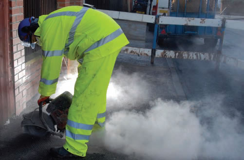 photo of man cutting concrete kicking up a lot of dust