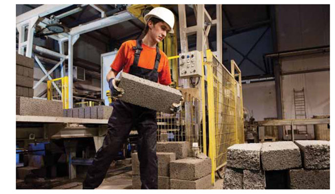 Image of worker lifting concrete blocks.