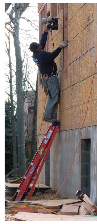 image of worker on ladder with nailgun