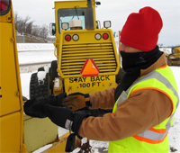 worker dressed for the cold in a jacket, scarf, hat, and gloves