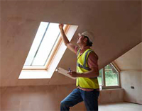 Photo shows worker inspecting a skylight following installation.