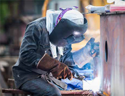 Photo shows welder wearing eye protection and gloves while welding a pipe connection.