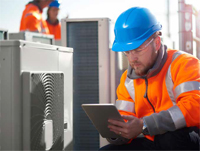 Photo shows worker with tablet computer making notes while inspecting an HVAC unit.