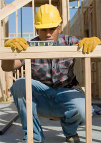 Photo shows carpenter at worksite using a level to check a header.