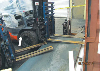 Photo of incident scene with forklift, forks lowered, with steel plate on ground in front of forklift, shipping container on far right of photo, in front of forklift.