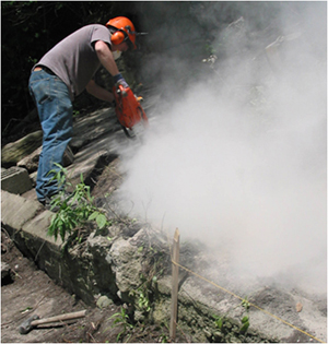 Man working with a chainsaw and silica dust