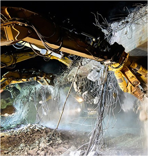 This is a picture of concrete Bridge Demolition with worker safely in enclosed vehicle