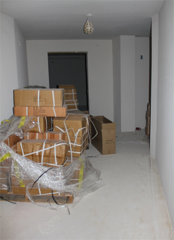 This is a photo of a hallway with a pallet piled with boxes and other boxes