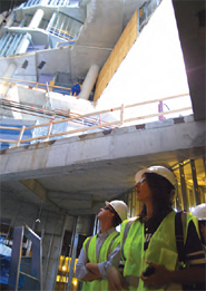 Photo of two construction workers in hard hats and vests at a site