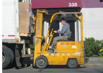 man driving a forklift, lifting a pallet fron a truck