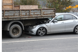 Picture of a car shoved under the rear end of a large truck