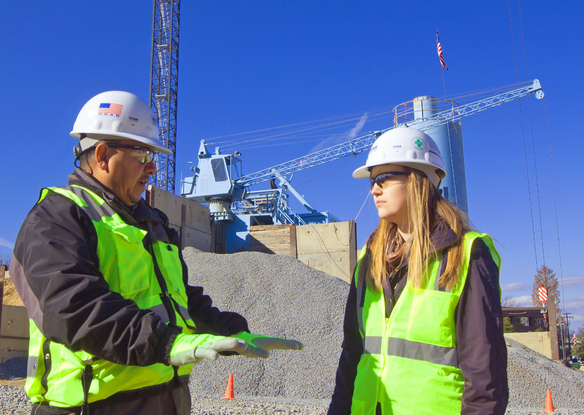 Safety officer discussing ongoing project with marketing coordinator